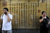 Gente utilizando su teléfono móvil este domingo en Pekín.
