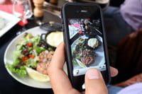 Un hombre fotografiando su plato de comida con su teléfono móvil, el 19 de julio de 2012 en París.