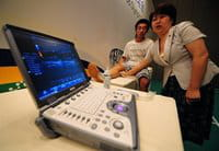Una técnico de producto utiliza un aparato de ultrasonido en una demostración de General Electric en Pekín