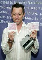 El actor estadounidense Alan Cumming muestra varias fotos realizadas con su Polaroid