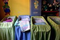 Un bebé duerme en una cuna de un orfanato
